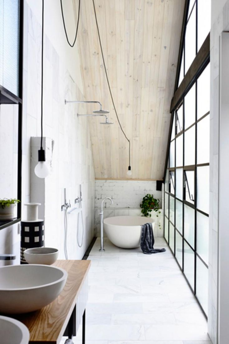 An unmistakably industrial feeling combines with natural timber and smooth curves to ensure the small bathroom space is welcoming.
