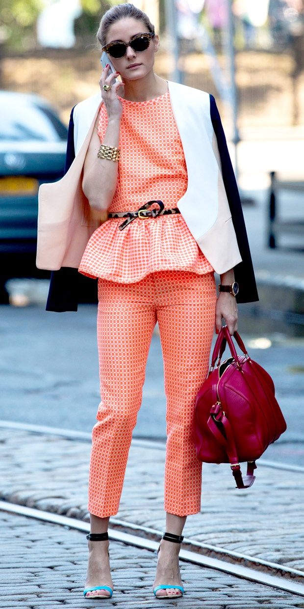 Olivia Palermo wears orange patterned peplum outfit. Blue/Black shoes. Red purse.