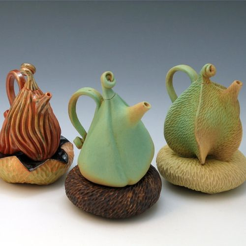 3 puffy pottery teapots on pillows by Roberta Polfus