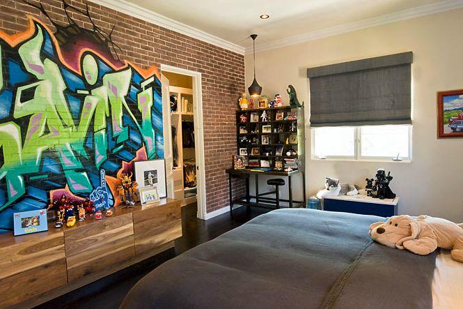 boy's rooms - brick wall graffiti art wood cabinet pale yellow walls black desk storage gray linen roman shade blue blanket Fun boy's bedroom