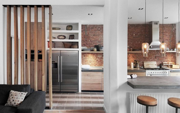 House refurbishment The Hague, The Netherlands. Exposed brick wall behind wooden kitchen with separate components.