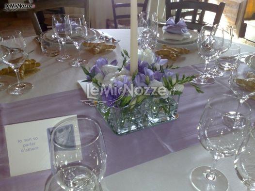 http://www.lemienozze.it/operatori-matrimonio/fiori_e_addobbi/il_giardino_fiorito/media/foto/10  Centrotavola con candela e fiori per il matrimonio sulle tonalità del lilla