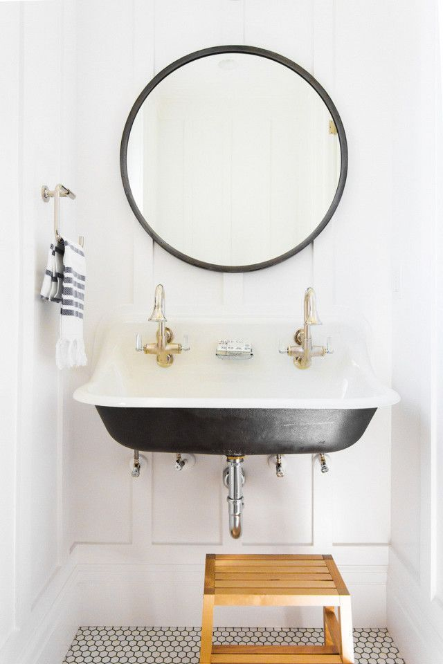 Kid-friendly bathroom with a step ladder, a wall-mounted sink, and an oversize round mirror hung against crisp white walls.