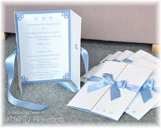 A simple gate fold design in ivory hammer finish card. The blue frame on the inside is Stampin' Up! Brocade Blue card, with a printed insert to match. The hearts and squares were dry embossed to the bride's design - I cut out multiple shapes in cardboard and stacked them together to create my own embossing die. Then stenciled the hearts in Brocade Blue ink. The centre heart on the outside of the invite has a clear Swarovski crystal on it. All tied closed with a Cornflower Blue satin ribbon.