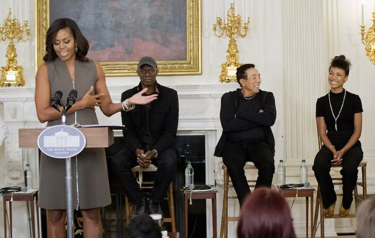 Michelle Obama with blues musician Keb' Mo', singer-songwriter Smokey Robinson, and jazz musician Esperanza Spalding in the State Dining Room of the White House during a student workshop for the 50th anniversary of the National Endowment for the Arts and Humanities.
