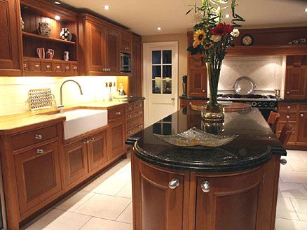 Traditional kitchen design - brown wood cabinets, apron front sink, black marble countertop, and light tile backsplashes and floor
