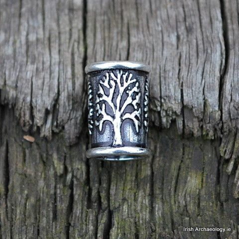 This sterling silver bead is decorated with a series of tree of life symbols.A distinctive piece of jewellery, it is worn by passing strands of hair through the central aperture. The bead can be worn on either beard or hair braids.