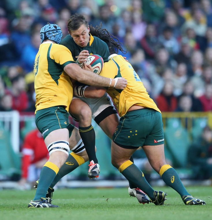Handre Pollard of South Africa is tackled by James Horwill and Saia Fainga'a