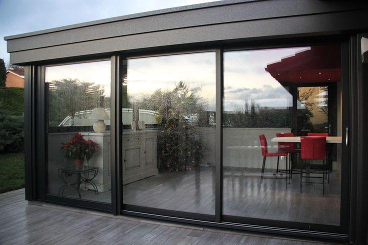 Extension véranda vitrée donnant sur terrasse à carrelage gris imitation parquet