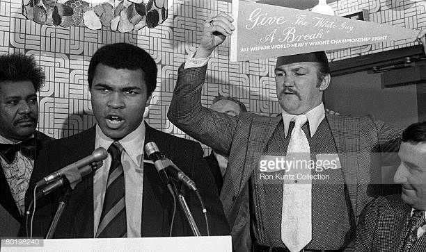 Heavyweight champion Muhammad Ali addresses the media while challenger Chuck Wepner holds up a pennant the reads 'Give the White Guy a Break' during...