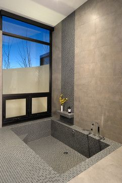 sunken tub!  Build your tub right into your bathroom floor by sinking it in below floor level. This tub is formed from concrete, then tiled for aesthetics and comfort. This can save you the hassle of installing a tub while giving you the benefits of a built-in feature — like the corner seat and step here.