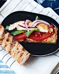 Open-Face Smoked-Mackerel Sandwiches.  Turks call these sandwiches balik ekmek and make them with grilled fish—like mackerel—from the Bosphorus. For his version, the grilled bread is spread with a creamy roasted-garlic puree and tops it with smoked mackerel, arugula and slices of red onion and tomato.