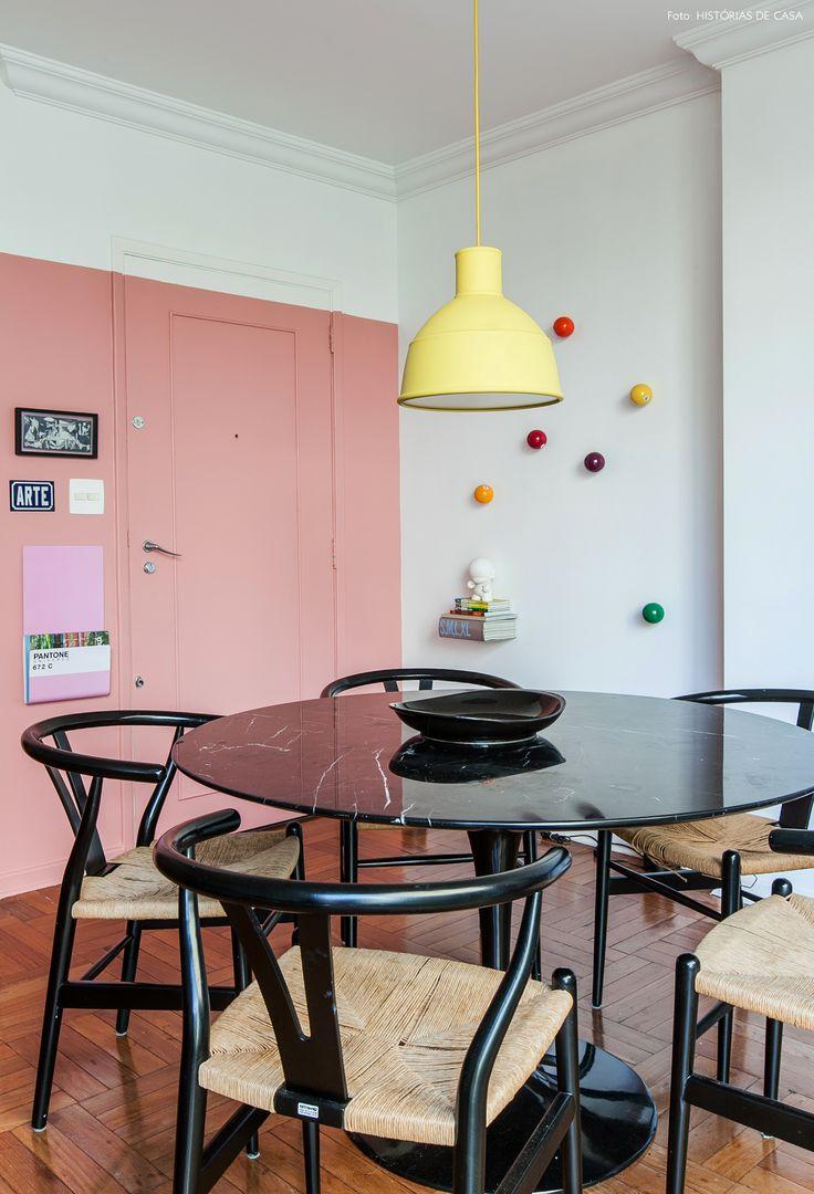 Sala de jantar tem parede pintada de rosa e ganchos de parede que simulam bola de bilhar e mesa saarinen preta.