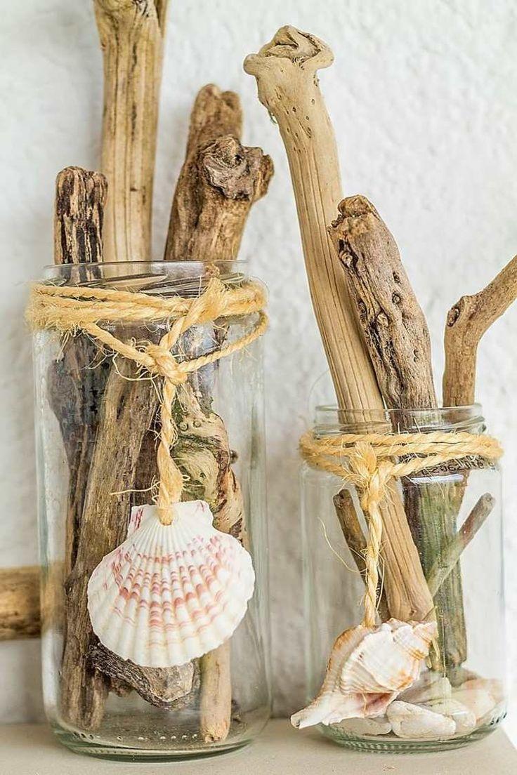 des bocaux remplis de bois flotté et décorés de coquillages et corde