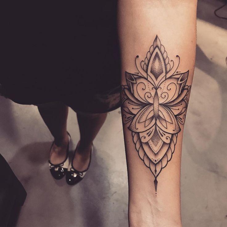 Tatuagem criada por Lucas Milk de Florianópolis. Flor de lótus com borboleta em preto e cinza no braço.