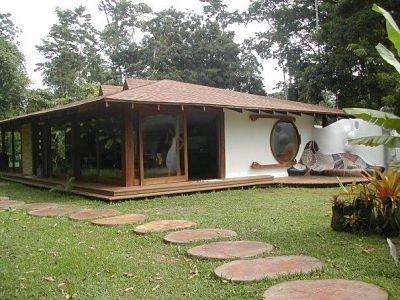 Casa de una sola planta con cocina, comedor y salón abiertos, dos dormitorios y dos baños exteriores. Si quieres ver más, visita OneDreamArt.com