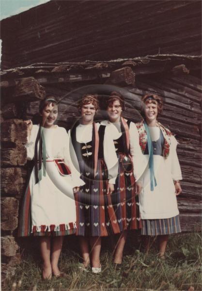 Huhukselaisia naisia kansallispuvuissa riihen nurkalla, 1962   Aiheen paikat:Pohjois-Karjala, Ilomantsi, Huhus, Kontiovaara   Ilomantsin Museosäätiö, esinenumero 156:479
