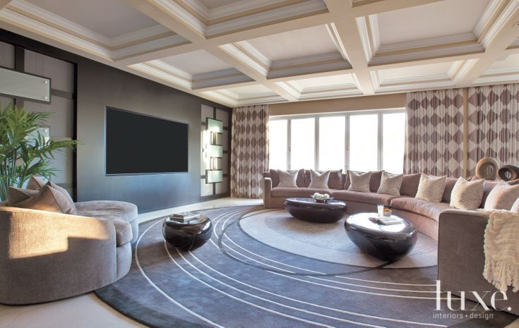 The family room's custom radial sectional covered in Kravet chenille cranks up the hangout volume and offers ample seating. Phillips Collection's black lacquer pebble tables become resting spots for drinks or feet, while underfoot, a custom wool rug echoes the curved pattern of the sofa.