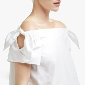 Off-the-shoulder necklines are almost always sexy, and while this one fits the bill, it's softened by two ties at the sleeves—meaning it reads romantic as...