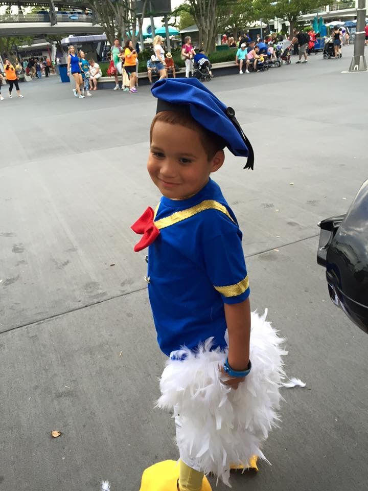 Donald Duck DIY costume. Purchased blue t-shirt, yellow legging (or pajama pant) and white shorts. Added braid and buttons to shirt. Added feather boas to shorts. Created hat. Felt for shoe cover/webbed feet. Results? One happy Donald Duck fan!