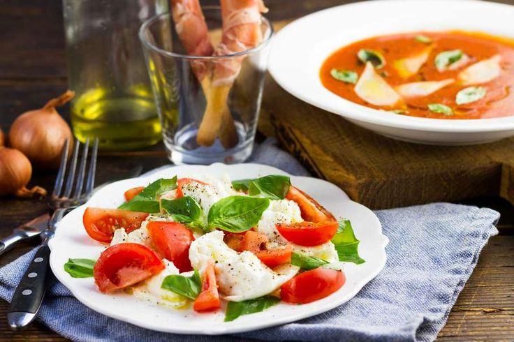 Recept voor huisgemaakte tomatensoep voor 4 personen. Met zout, water, olijfolie, peper, groene pesto, rauwe ham, mozzarella, parmezaanse kaas, soepstengel, trostomaat, ui, basilicum en knoflook