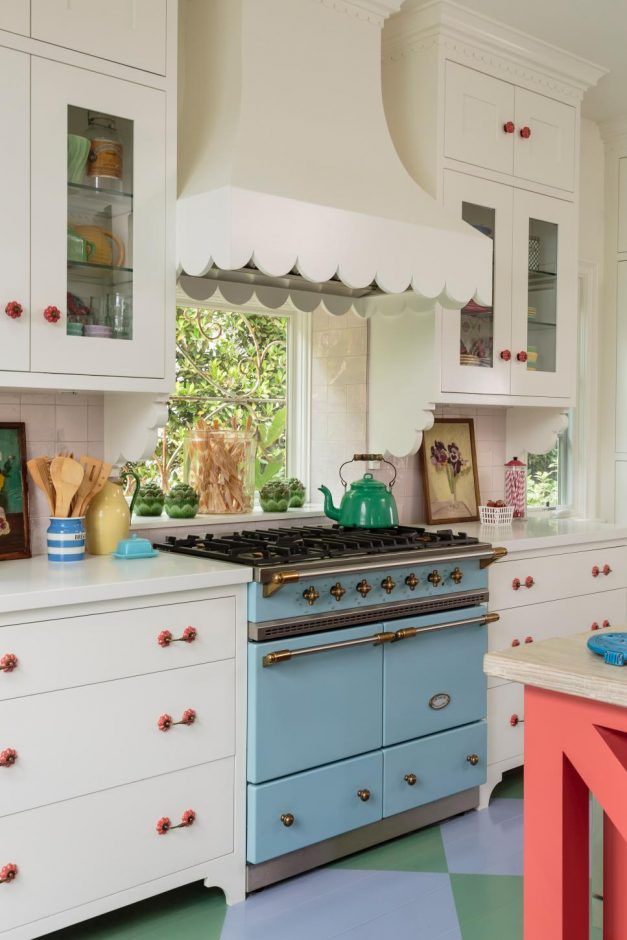 Kitchen: Blue Retro Dual‐Ovens And Scallop‐Edged Ventilation System Add Character To Vibrant Kitchen. retro appliances. blue gas stove. white kitchen cabinet. pink kitchen island. traditional kitchen. pink drawer pulls. tile flooring.