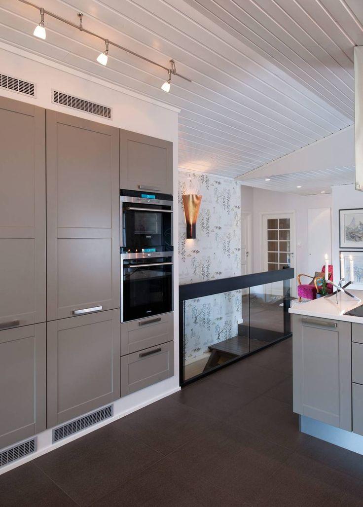 INTEGRERT: Skap, skuffer og hvitevarer er integrert i veggen, og gjør kjøkkenet ryddig. Fargen på kjøkkenfronten er i en dus gråbrun tone, som skaper varme mot det hvite. I bakgrunnen ser vi glassgelenderet til trappen ned.