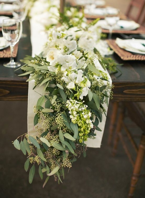 """Garland table runner. I think this is seeded eucalyptus. Mix in with votives, maybe some fairy berries and wine bottles or wine glass """"candlesticks"""" or use the black lanterns"""