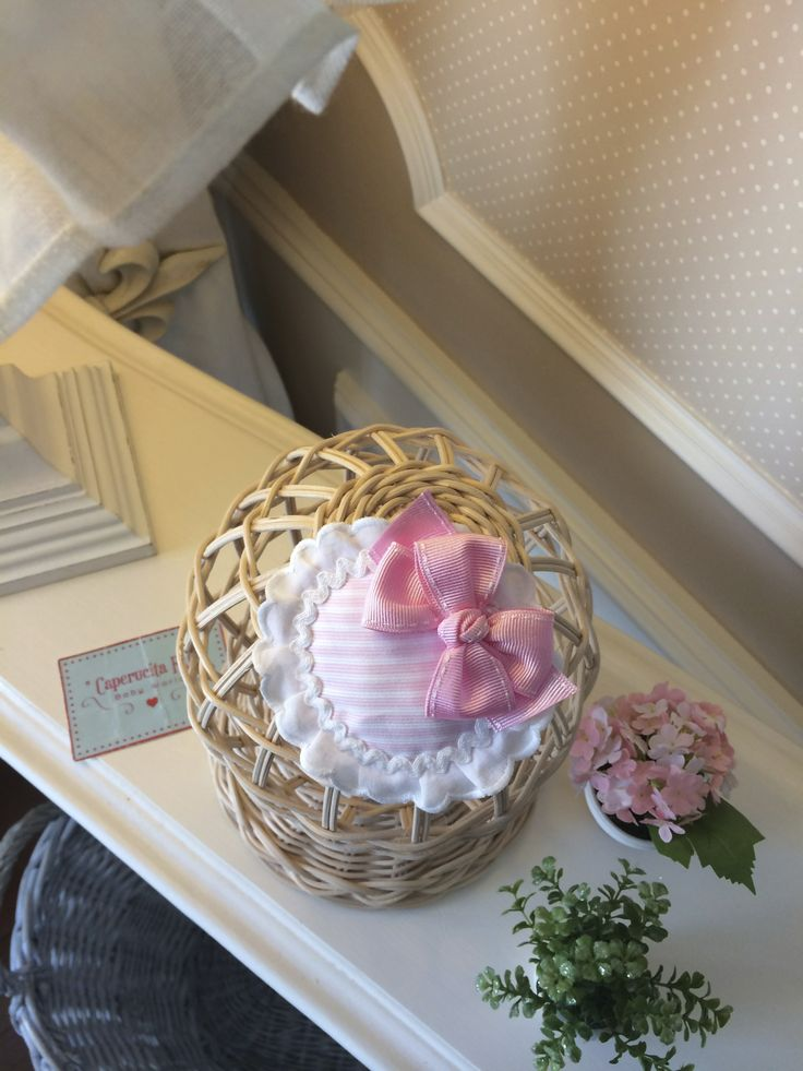 Tocado con base de tela de rayas rosas y blancas, tira bordada blanca y lazote a juego.