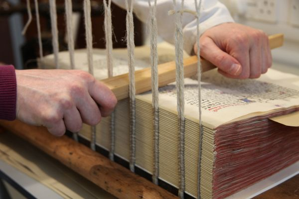 W7: Rebinding a manuscript (Fitzwilliam MS 251) using a sewing frame. The use of a sewing frame has been in use since the 12th century. Public domain.