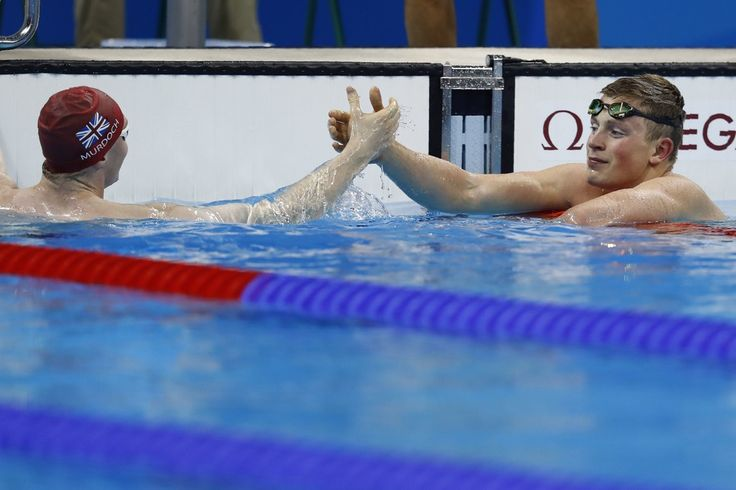 Britain's Adam Peaty (R) celebrates with Britain's Ross Murdoch after breaking the world record in the Men's 100m Breaststroke heat during the swimming event at the Rio 2016 Olympic Games at the Olympic Aquatics Stadium in Rio de Janeiro on August 6, 2016.   / AFP / Odd Andersen