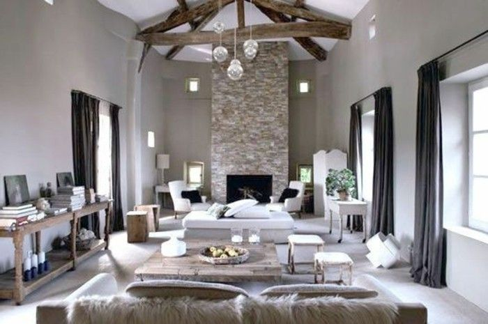 large living room, with big fireplace, wooden beams on ceiling, creamy pale grayish-brown walls, living room paint colors, wooden furniture and dark curtains
