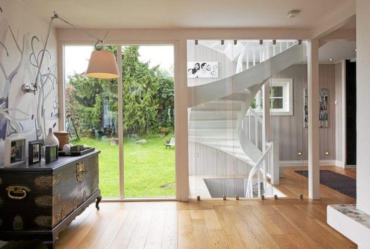 GLASSVEGG: En lang bærevegg skiller kjøkken og stue i denne boligen. Endeveggen i glass gjør et poeng ut av den vakre trappen. Den lange, smale stuen krevde en helt spesiell sofa.
