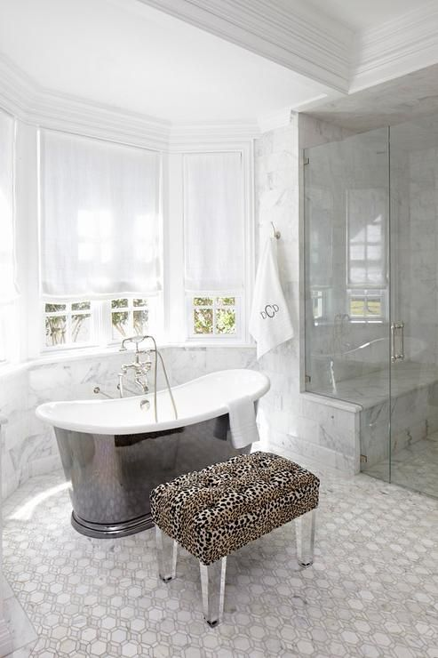 Gorgeous master bathroom features a bay window dressed in white roman shades is filled with a cast iron freestanding tub and vintage style tub filler as well as a cheetah bench on lucite legs atop a mosaic marble tiled floor.