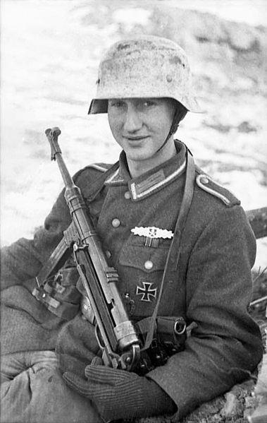 Sowjetunion.- Unteroffizier (ausgezeichnet mit Nahkampfspange, Band der Ostmedaille) mit Maschinenpistole MP 40 in Winterlandschaft, sitzend; PK 697