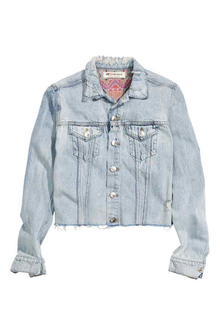 Jeansjasje: H&M LOVES COACHELLA. Een kort jeansjasje van gewassen denim met forse slijtagedetails. Het model heeft borstzakken met een klep en knoop en een afgeknipte, onafgewerkte rand aan de onderkant.