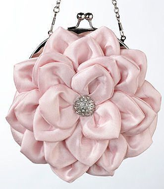 This pink satin purse is perfect for carrying your wedding day essentials. It is shaped like a flower and touched off with a silver rhinestone decoration. The purse has a metal snap closure. You can c
