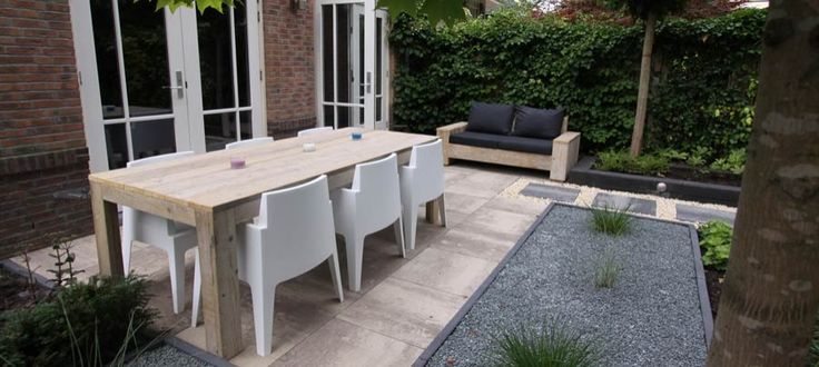Steigerhouten tafel met witte stoelen.