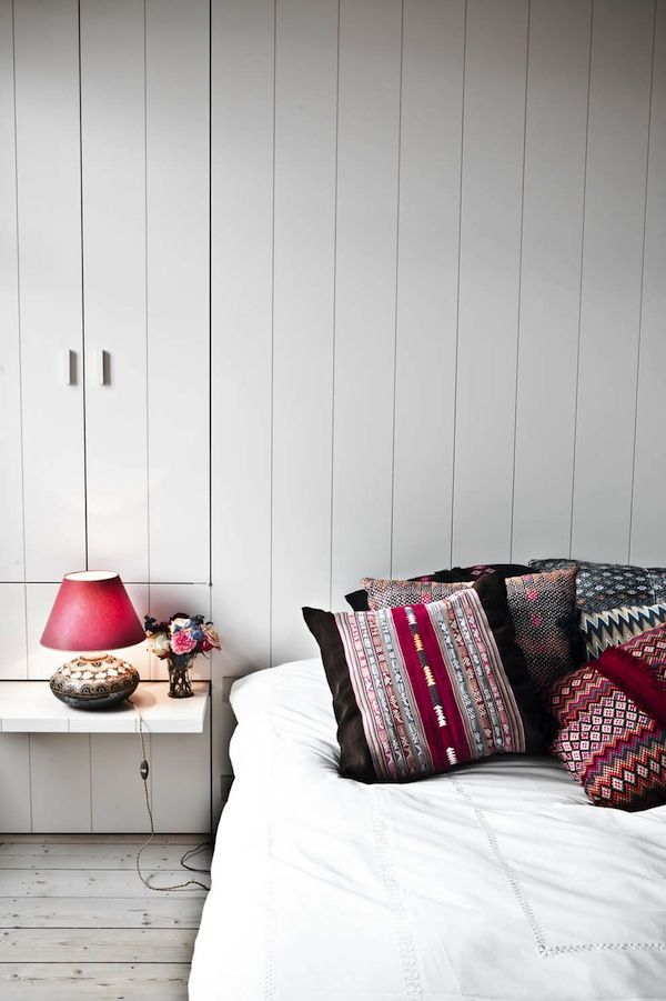 Maffigt med mönster mot det vita.    White room, beautiful textiles, love the bedside shelf.
