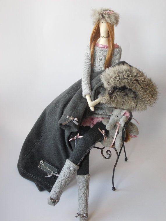 Muñeca Tilda Perla es 25 pulgadas (65 cm) alto.  Ella lleva abrigo de pelo de camello con vestido de lana, encaje y piel. El pelo está hecho de pelos artificiales  Esta encantadora muñeca puede decorar su casa o ser un excelente regalo. Cada muñeca es única.  Se llena con relleno de fibra poliester hipoalérgico (como perla).