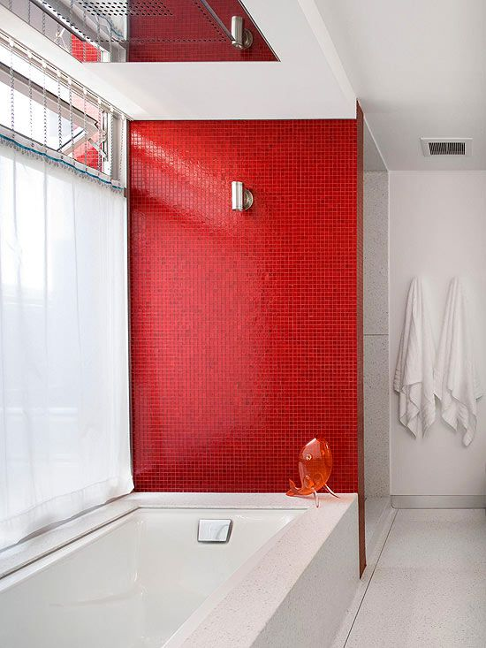 Rich red is not the typical color used in a bathroom, but when used correctly the hue can exude style and pizzazz. Here, a wall of tiny red mosaic tiles adds colorful character to this nearly all-white modern-style bathroom. The tile not only adds a splash of needed color, but it also reflects light streaming in from the large window nearby./