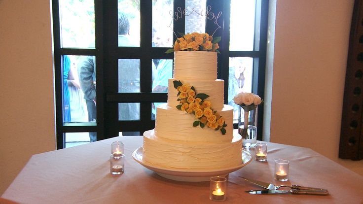 White 4-tier wedding cake accented with petite yellow roses.