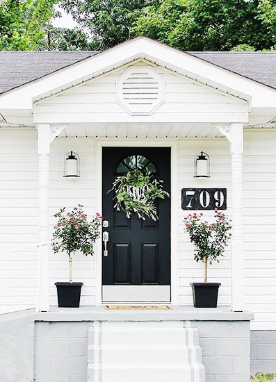 Striking black front door on class white house, wreath, planters with topiaries, and big house numbers - thistlewoodfarms