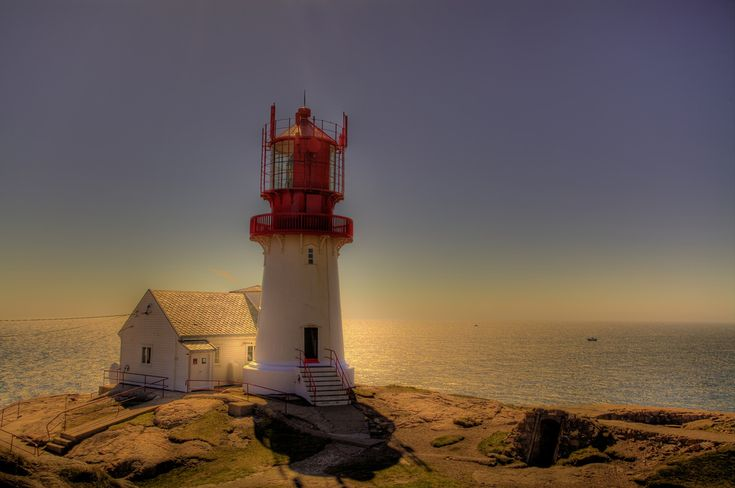 https://flic.kr/p/7ZMQHc | Lindesnes fyr | Lindesnes fyr is a coastal lighthouse on the southernmost tip of mainland Norway, the peninsula Neset. It is also the oldest lighthouse station in Norway, first lit in 1655. To avoid confusion with the lighthouse at Skagen in Denmark, it was lit in conjunction with Markøy fyrstasjon. It has gone through several changes since it was built: In 1822, it was refitted with a coal lamp, and in 1854 a new lamp was installed with the current lens