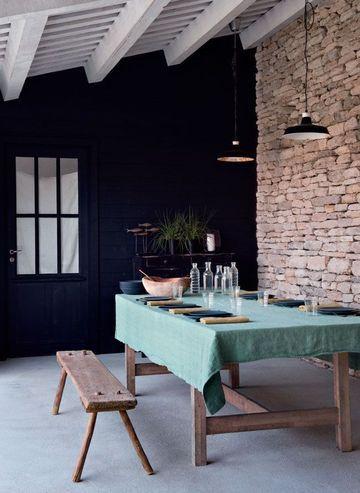 """teinte """"Railings"""" de Farrow & Ball, la salle à manger d'été a été aménagée sous un auvent. Table et banc chinés. Suspensions Ikea. Nappe en chanvre teinté et serviettes anciennes, Longmétrage. Bouteilles et verres, Seletti."""