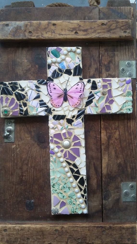 This mixed media mosaic cross has been constructed using recycled items. The base of the cross was made from hand cut pallet wood. It has been decorated using broken pieces of china, dishes, and jewelry and has been arranged in a unique style. The pieces are first glued to the cross and a beige grout has been added for definition, durability, and stain resistance. Each cross has hanging hardware on the back. No two crosses are alike. The main focal point is a purple butterfly. Primary colors…