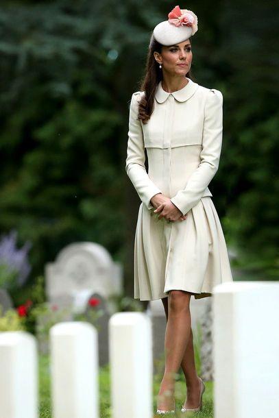 """Kate Middleton trug einen beigen Hut mit einer großen rosafarbenen Blüte, kombiniert mit einem schlichten beigen Kleid ihres Lieblingsdesigners Alexander McQueen Anfang August 2014 auf der """"St Symphorien Military""""-Zeremonie in Belgien"""