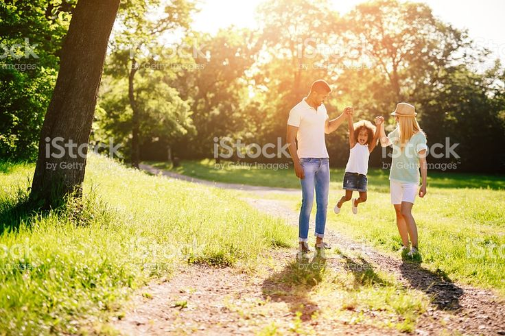 Mother and father swinging daughter royalty-free stock photo