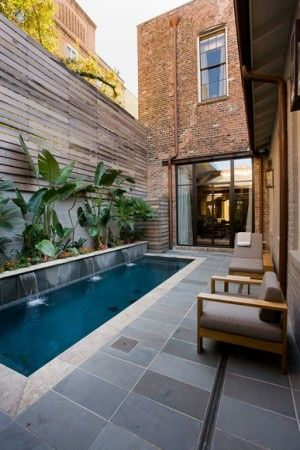"""small backyard. Blues & greys and woods. High wall with plants & herb garden and a small """"endless"""" exercise pool."""