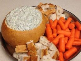 Spinach Dip made with Knorr dry vegetable soup mix.  Served in a sourdough bread bowl with bread and carrots,